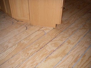 Close up of plywood subfloor with tubing for flooring heat