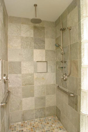 A grey tile shower with an overhead rain shower head