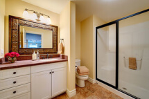 The bathroom vanity with LG HiMacs counters and white cabinets.