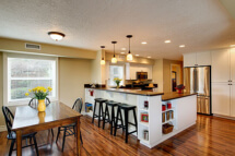 This daylight basement remodel features a kitchen with an eating bar.