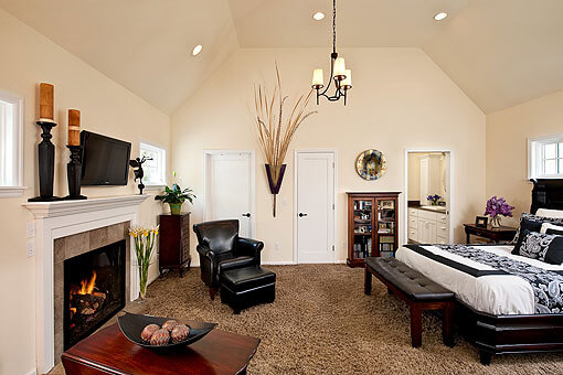 The entry to the master suite opens into a large bedroom with a vaulted ceiling and ample natural lighting.