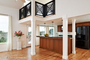 The black railing accents the loft above this stylish new kitchen remodel