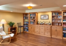 This basement retreat has a coffered ceiling and built-in cabinetry for both a bar and game/book storage.