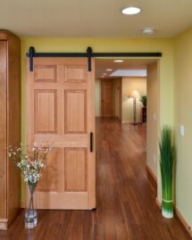 A sliding barn door is hung using classic flat track hardware is from Rustica Hardware. Stained bamboo flooring is from Arcade.