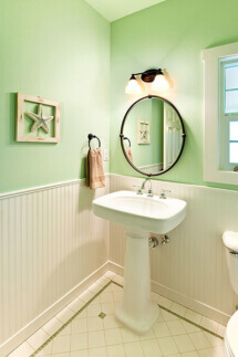 White wainscoting, sea foam green walls, and a pedestal sink lend a spacious feeling to this small powder room.