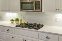 Caesarstone countertops and a white subway tile backsplash complete the look in this white schoolhouse kitchen.