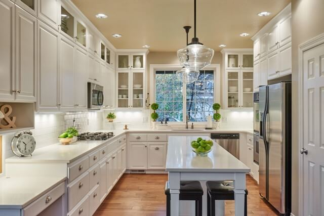 Hand-scraped maple floors work beautifully with the new white kitchen cabinetry.