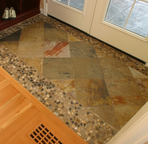 The new back entry floor tile bordered in river pebbles is beautiful and practical.