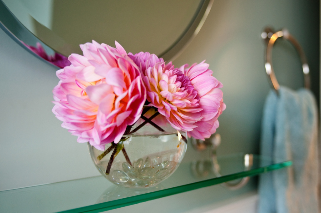 A flower and glass shelf in a bathroom remodel by design and build remodeling contractor Powell Construction