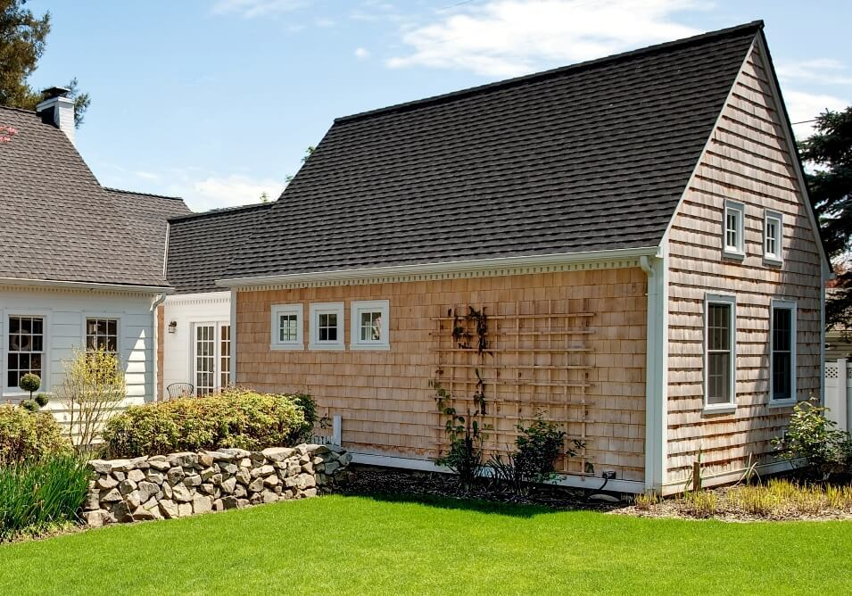 Alaskan cedar siding is left unpainted in true Cape Cod style. It will turn to a weathered grey.