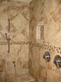 A walk-in shower features a tiled bench and niches.