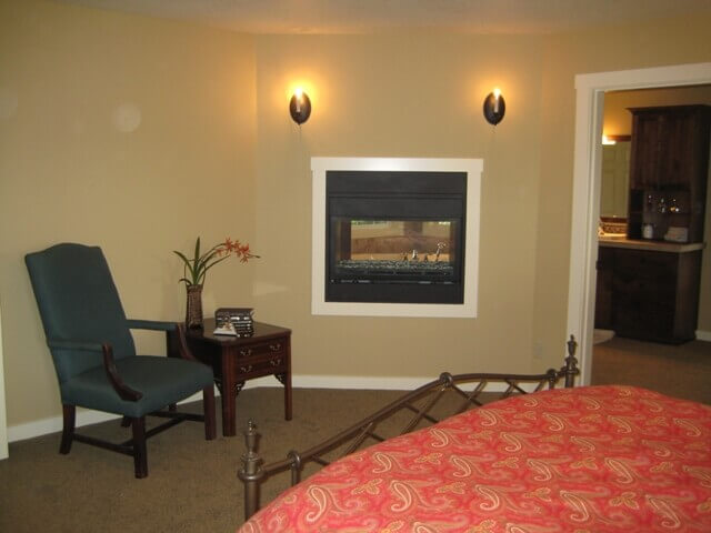 A two-sided fireplace both warms the bedroom and master bath.