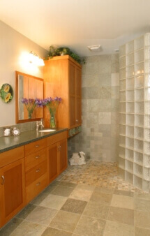 The remodeled master bath features a walk-in tiled shower with an angled glass block wall.