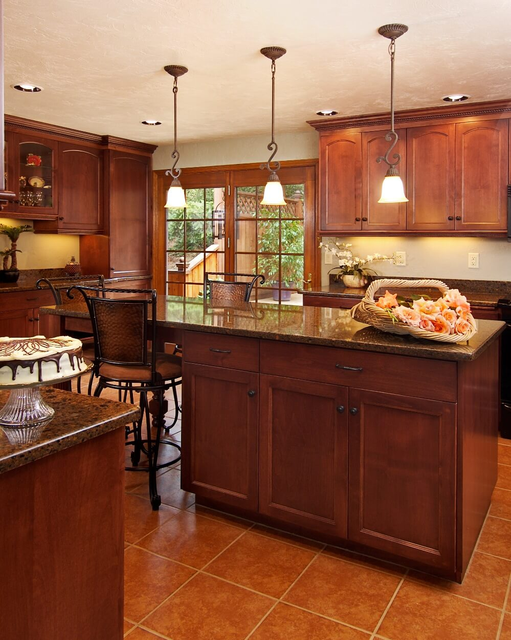 This kitchen design features dark cherry stained cabinets, black appliances, and Cambria counters.