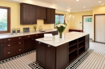 An expansive laundry remodel with black and white tile floor and yellow paint.