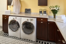 A yellow laundry with dark stained cabinets.