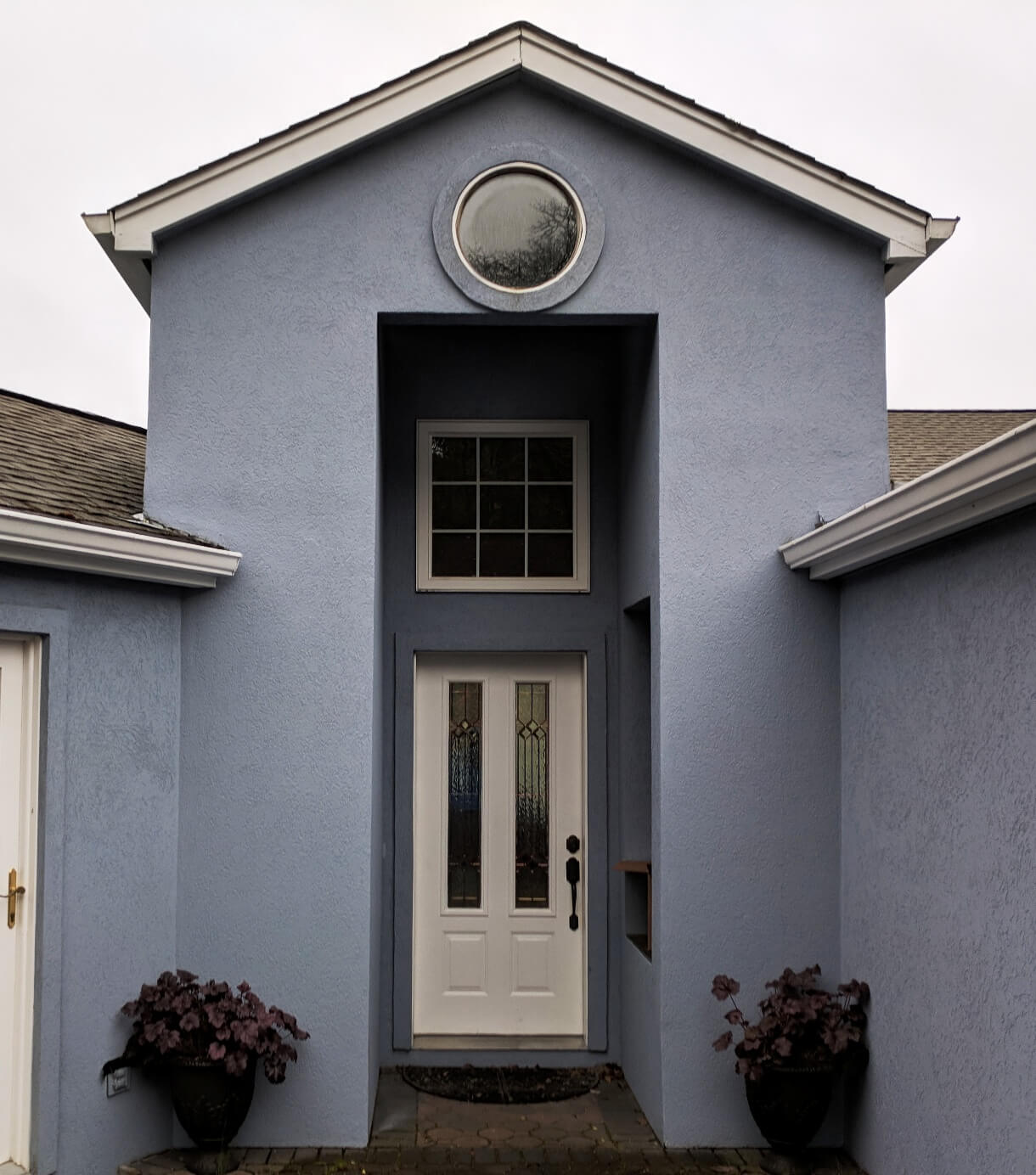 Stucco replaces the vertical siding to complete the exterior face lift of this renovation.
