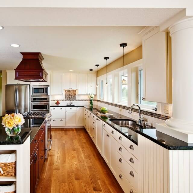 The kitchen design features white perimeter cabinets and richly stained island cabinets.