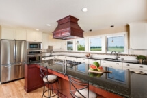 A granite-covered island with sapele cabinets is the centerpiece of the new farmhouse kitchen.