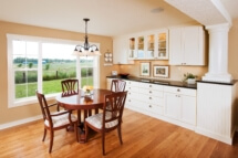 A custom white buffet in the dining room and white columns that support the beam concealed in the ceiling.
