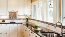 A wall of windows floods the farmhouse-style kitchen with natural light while pendant lights illuminate the counter.
