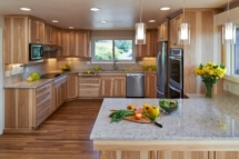 Pendant lights over the peninsula add a modern touch to this wood-themed kitchen remodel.