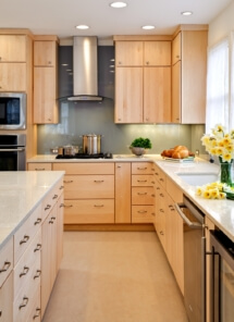 A maple kitchen with a backsplash using architectural glass. Caesarstone countertops, and flat-slab cabinet doors and drawers made of maple