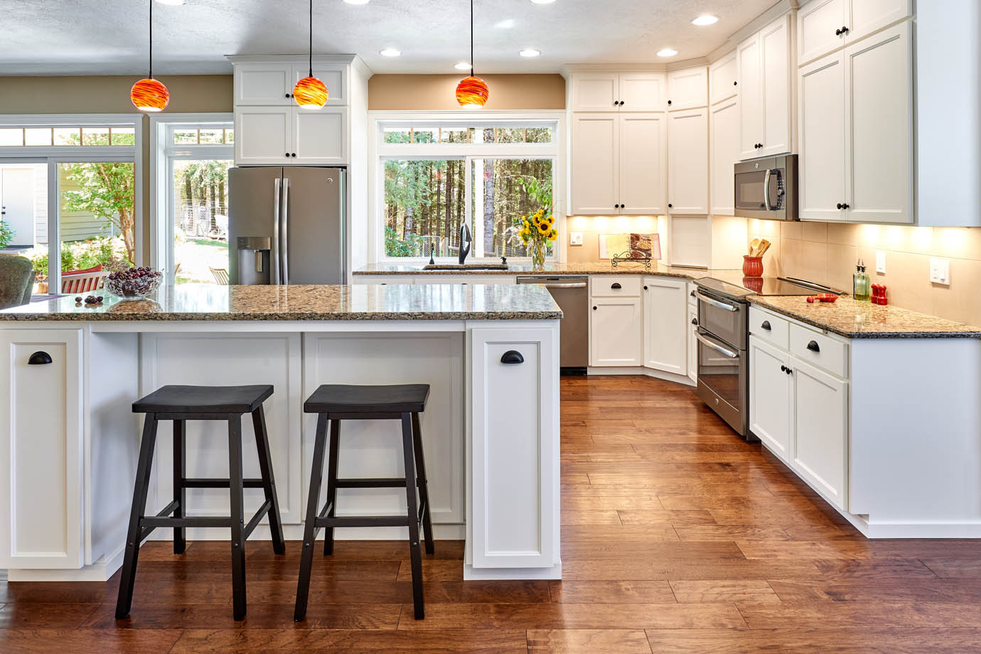 Design-Build remodeling contractor Powell Construction designs a white kitchen with many windows, stone countertops, and pendant lighting.
