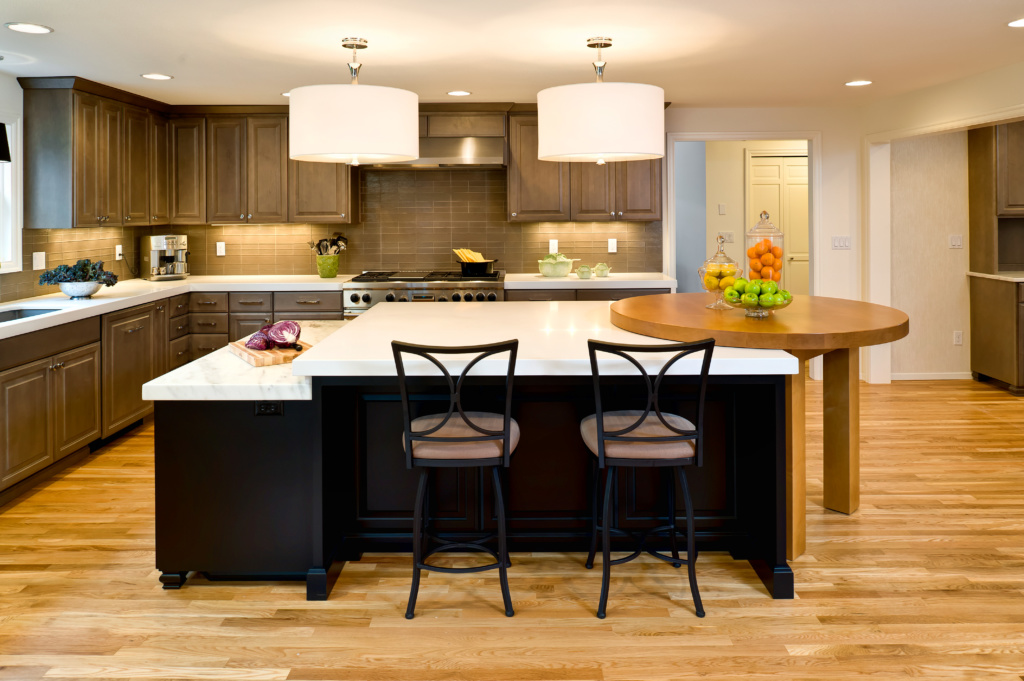Contemporary kitchen renovation with raised island, grey cabinets, and kitchen island with built-in table.