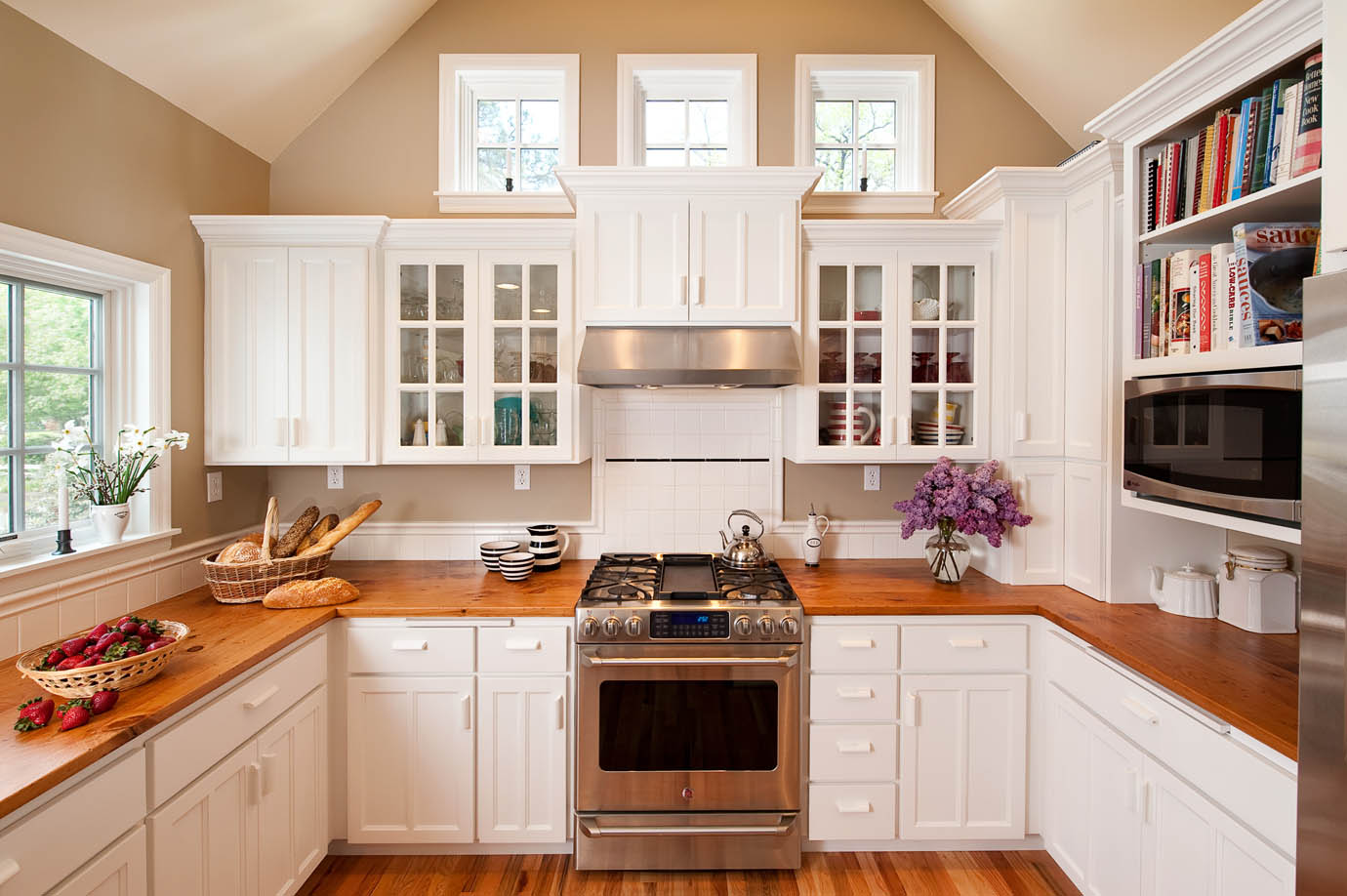 Kitchen design featuring pine counters, clear story windows, and glass doors in this Cape Cod white kitchen remodel by renovation contractor Powell Construction.