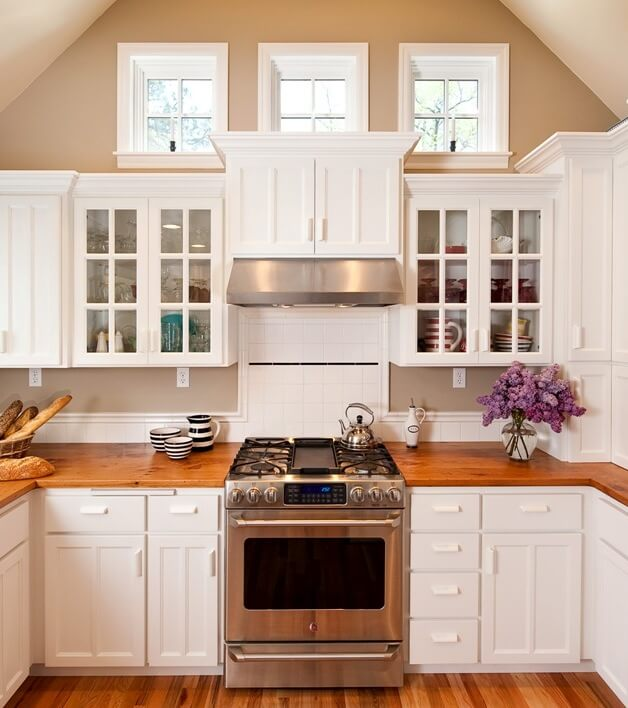 This classic white Cape Cod kitchen addition features small but important design details such as crown molding and staggered cabinet heights.