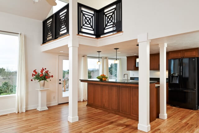Loft with black railing in geometric pattern above kitchen.