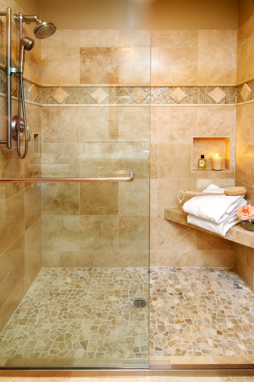 A walk-in travertine shower includes a corner bench and recessed niches.