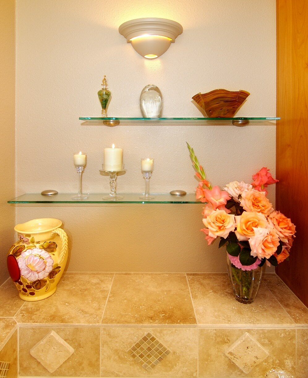 A small bath remodeling idea is glass shelves, which provide additional display space without blocking light.
