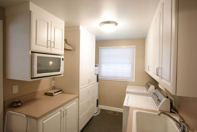 The laundry area with laminate counters and white cabinets.