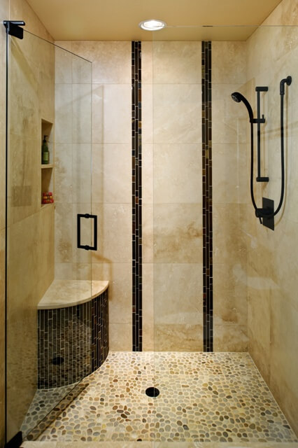 "The remodeled bathroom features a stunning shower with accent tiles installed vertically to evoke the look of bamboo. The floor tile is United Tile Island Pebbles ""Maluku Tan"""