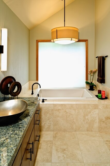 The master bath design specified a travertine tub surround for elegance and durability and the pendant light is from