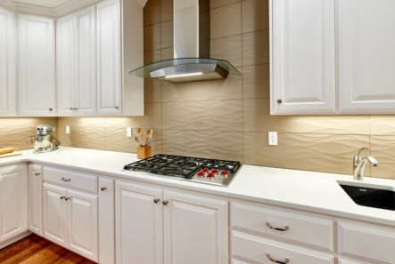 The cooking workstation in this kitchen remodel features a Wolf cooktop and Zephyr Ravenna hood, along with a Blanco Precis prep sink..