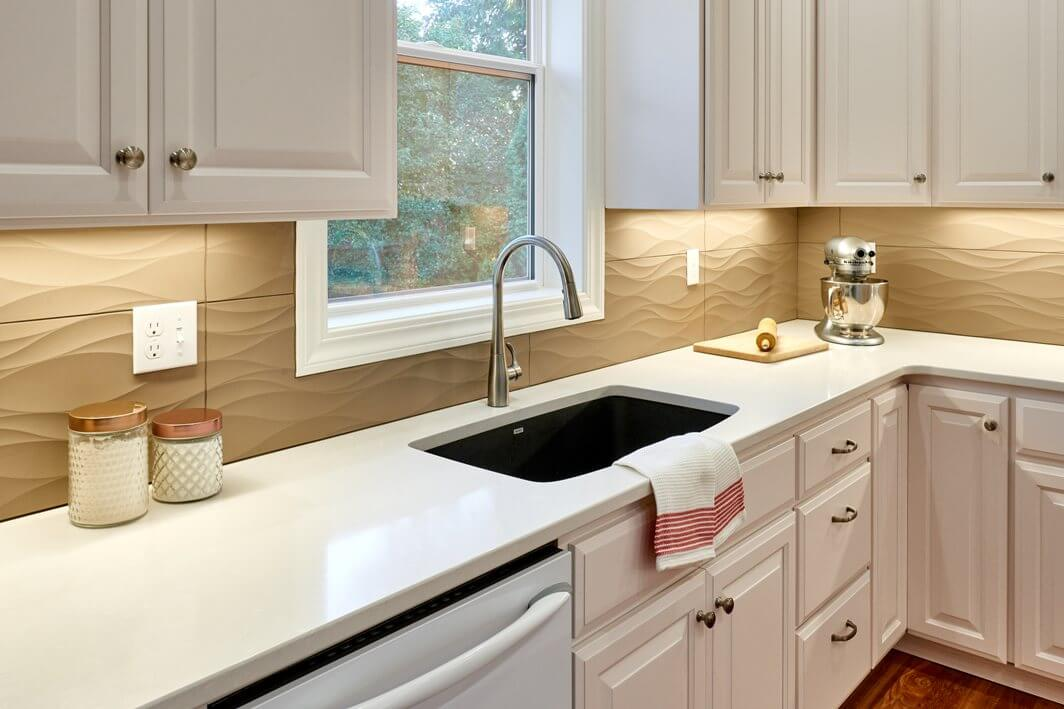 The cleaning workstation in this kitchen renovation features a Blanco Valea undermount sink and Kohler Simplice faucet.
