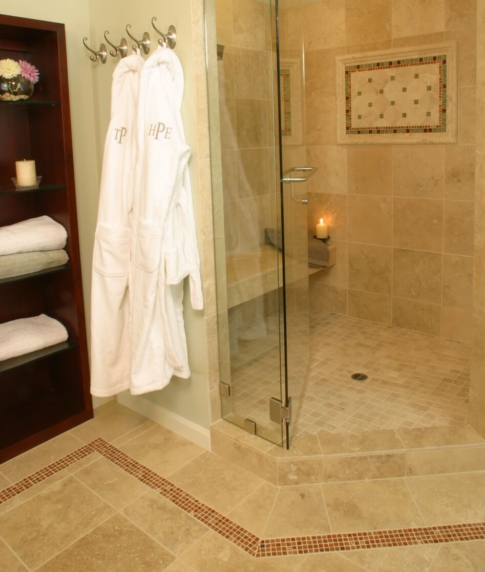 A luxurious shower includes a Travertine seat, recessed niches, an adjustable hand held shower sprayer, and a beautiful inlaid tile mural.
