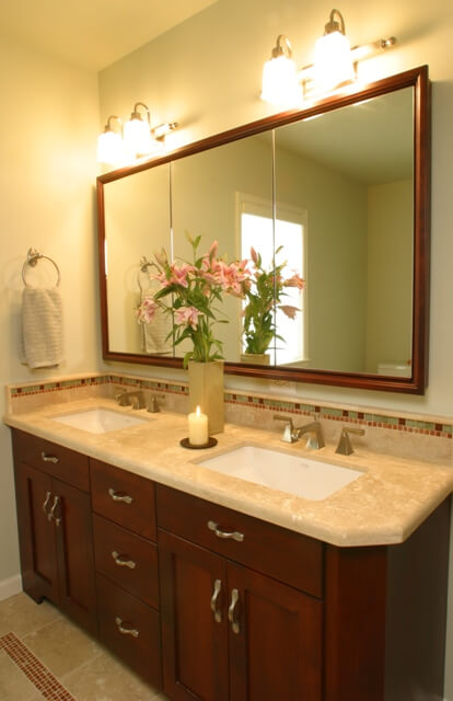 This travertine master bath vanity features a richly stained wood and travertine tile countertop.