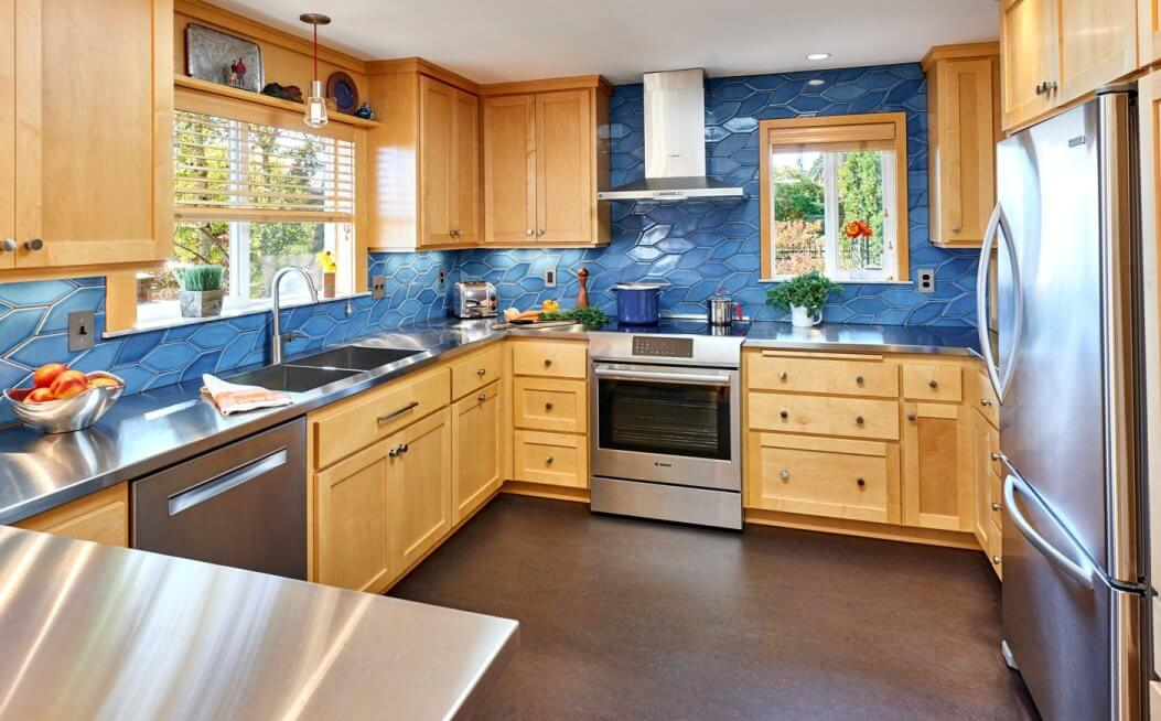 kitchen design with fireclay blue tile, stainless steel counters, and maple cabinets