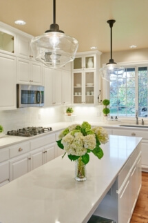 The new kitchen design features one long island with pendant lights above.