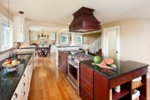 Kitchen has a center island stained dark and perimeter cabinets in off-white.