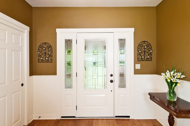 The lovely front door is painted white and has two glass sidelights.