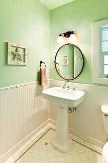 A sea foam green powder room with a beach theme, a pedestal sink, and white wainscotting.
