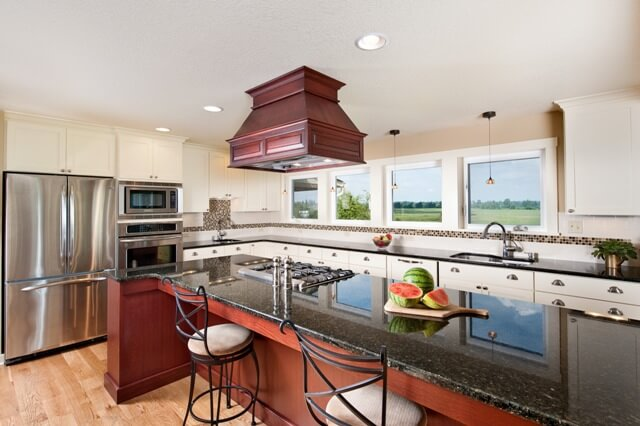 The farmhouse kitchen has an abundance of natural light, granite countertops, and two concealed dishwashers.