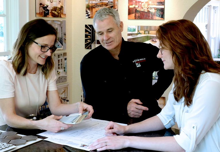 Contractor Tom Powell meets with designer and client choosing samples