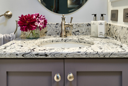 quartz countertop sits on custom gray vanity cabinets with brushed nickle waterfall faucet