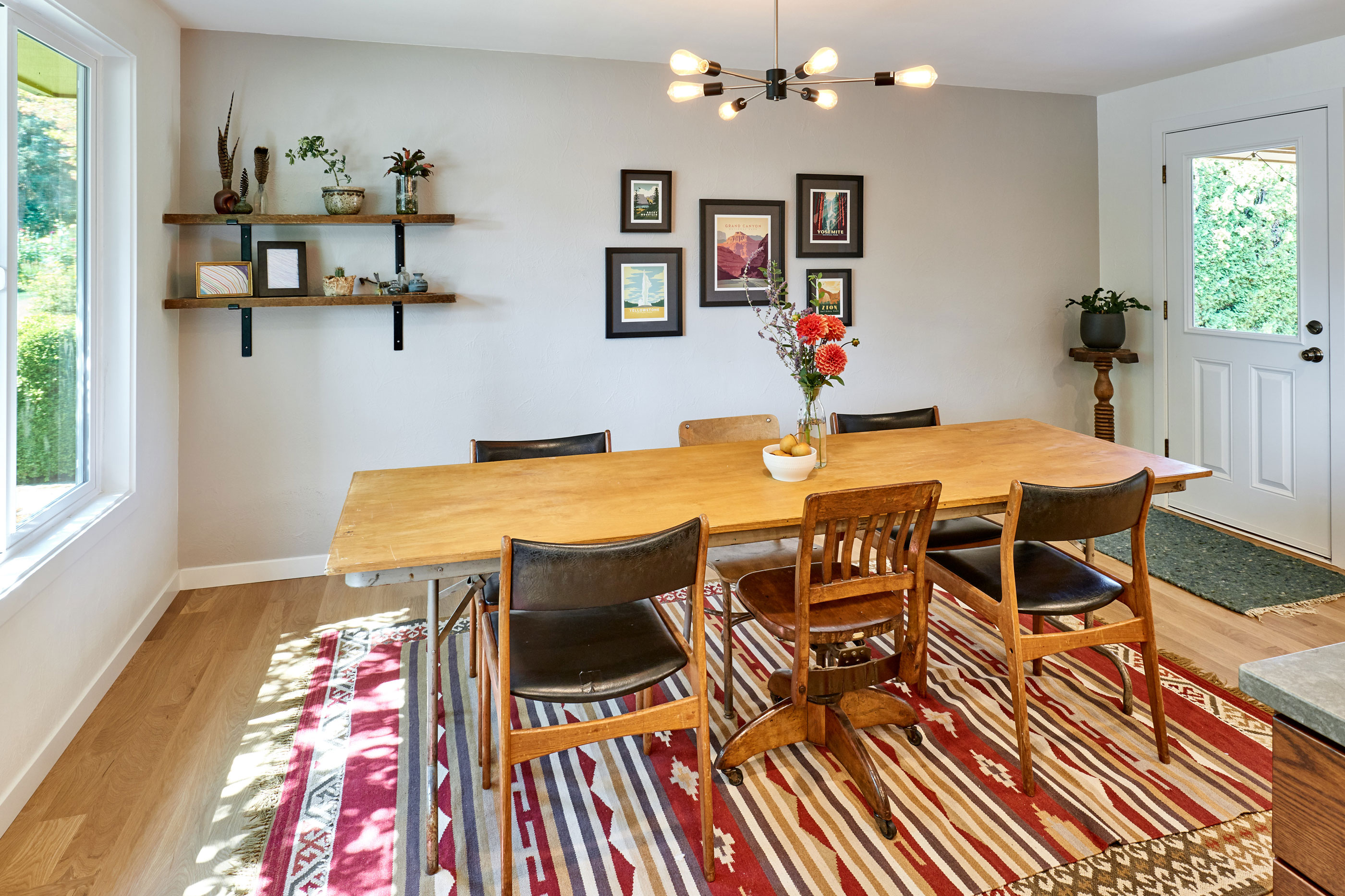 wooden dining table on aztec print rug with modern light fixture overhead